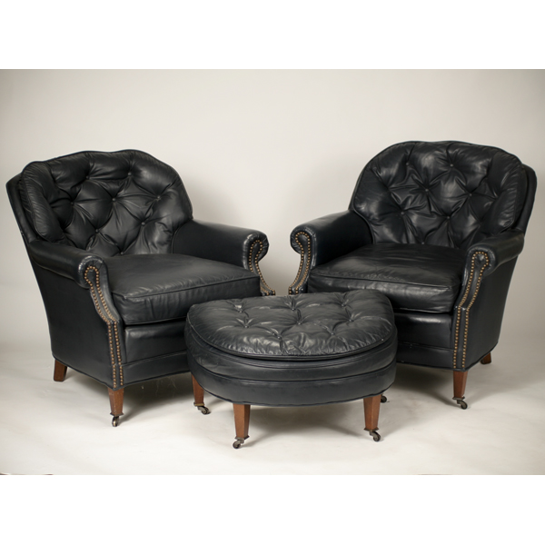 Two midnight blue button tufted leather club chairs with ottoman