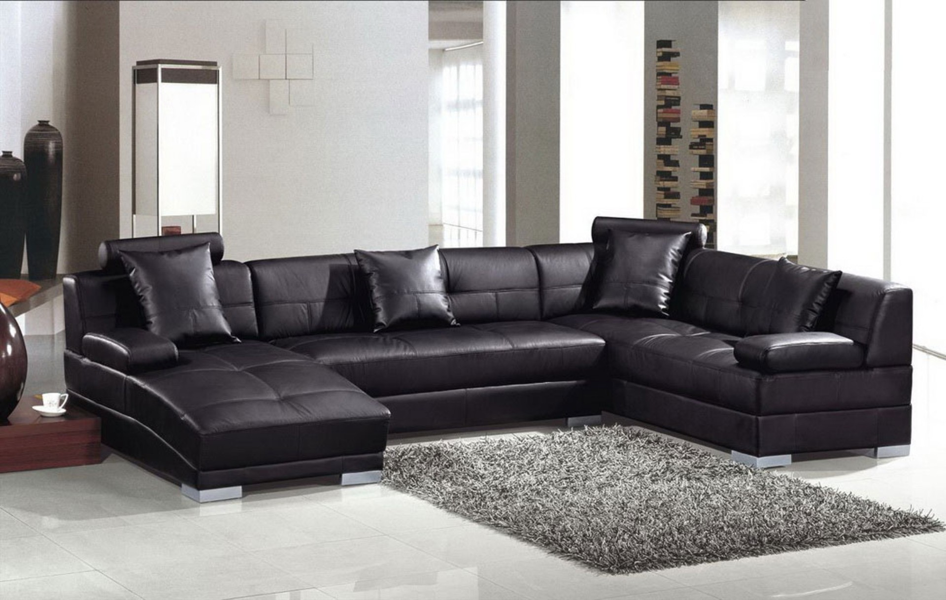 Black Leather Sleeper Sectional Sofa With Cushions And Silver Steel Legs  Placed On The White Floor