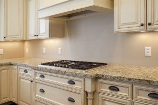 Love the antiqued cream cabinets and light countertop combo | For