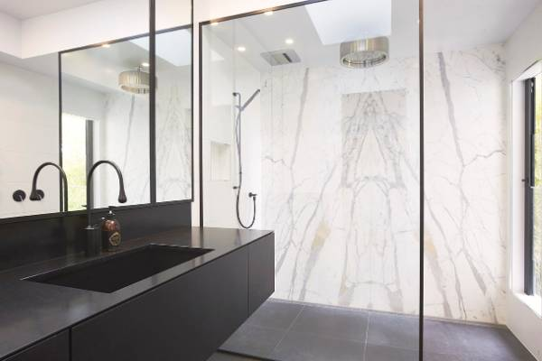 Black and white bathroom comes with black taps, shower and toilet
